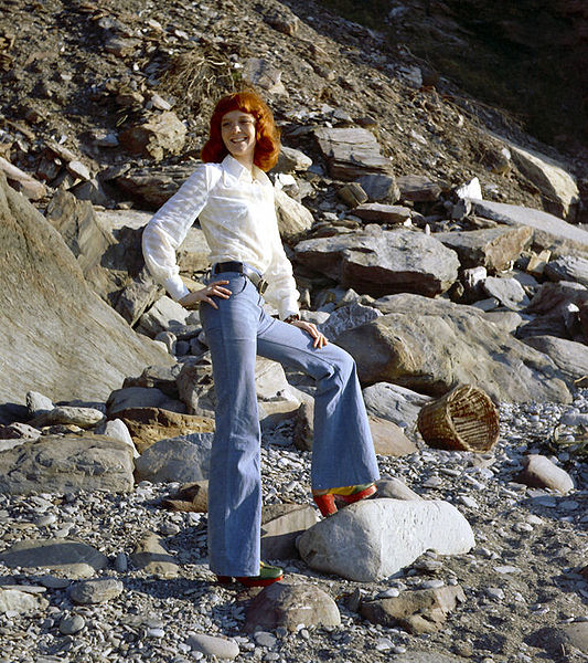 woman wearing bell bottom jeans with platform shoes standing on the beach